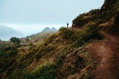 Fotvandrarekonturn ser in i dalen och lyssnar till tystnaden Dimma och mist hänger över bergmaxima på arkivfoto