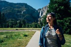 Fotvandrarekvinna i hatt som går i bana i skog royaltyfria foton