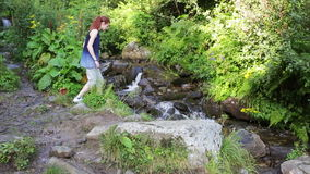 Fotvandrarekvinna med ryggsäcken som går på en skogslinga i bergen på bakgrunden en vattenfall fotvandra Affärsföretag in lager videofilmer
