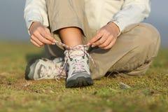 Fotvandrarekvinna som binder skosnöre av kängor Royaltyfria Bilder
