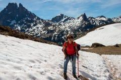 Fotvandrarekvinna som går i snön, i franska Pyrenees berg, Pic du midi D Ossau i bakgrund arkivfoto