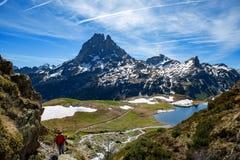Fotvandrarekvinna som g?r i de franska Pyrenees bergen, Pic du midi D Ossau i bakgrund royaltyfri fotografi