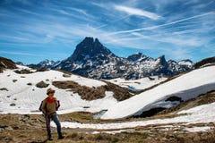 Fotvandrarekvinna som g?r i de franska Pyrenees bergen, Pic du midi D Ossau i bakgrund royaltyfri foto