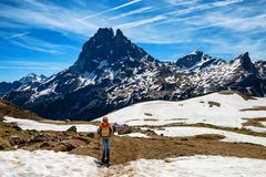 Fotvandrarekvinna som g?r i de franska Pyrenees bergen, Pic du midi D Ossau i bakgrund royaltyfria foton