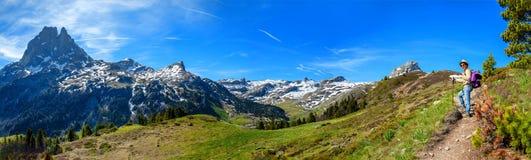Fotvandrarekvinna som g?r i de franska Pyrenees bergen, Pic du midi D Ossau i bakgrund royaltyfria bilder