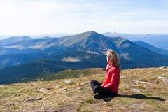 Fotvandrarekvinna som sitter på en halt i bergen arkivbild