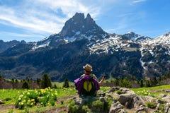 Fotvandrarekvinna som vilar och ser Pic du Midi Ossau i de franska Pyrenees bergen royaltyfri fotografi