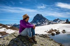 Fotvandrarekvinna som vilar och ser Pic du Midi Ossau i de franska Pyrenees bergen arkivbild