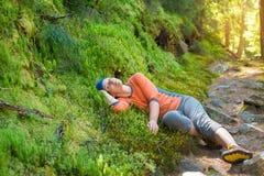 Fotvandrarekvinnan har gyckel, medan hon vilar Arkivbild