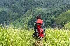 Fotvandrarekvinnan klättrar upp det sista avsnittet i berg Handelsresande som går i utomhus- livsstilaffärsföretag arkivfoto