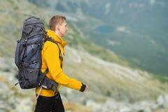 Fotvandrareman med den stora ryggsäcken i berg arkivbilder