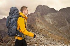 Fotvandrareman med den stora ryggsäcken i berg royaltyfri foto
