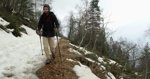 Fotvandrareman med ryggsäcken som går på den snöig slingabanan Följande framdel Verklig fotvandrarefolkvuxen människa som in fotv lager videofilmer