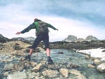Fotvandrareman med ryggs?ckkorsningen str?m p? stenar i Dolomiti royaltyfri bild