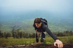 Fotvandrareman som klättrar en brant vägg i berg arkivbilder