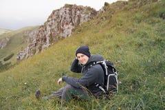 Fotvandrareman som kopplar av i berg royaltyfria foton