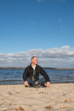 Fotvandraremansammanträde på stranden och att le, koppla av och tyckande om l Royaltyfria Foton