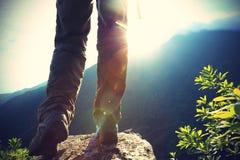 Fotvandraren för den unga kvinnan lägger benen på ryggen på soluppgångbergmaximum Arkivfoton