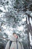 Fotvandraren för den unga kvinnan som upp till ser, sörjer filialer i täckt snö för vinter skogen Royaltyfri Foto