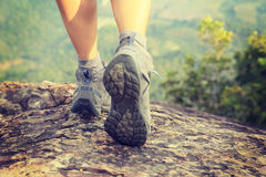 Fotvandraren för den unga kvinnan lägger benen på ryggen klättring på bergmaximumet Royaltyfri Bild