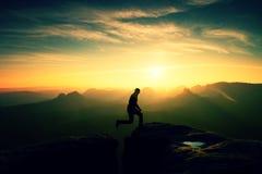 Fotvandraren i svart hoppar mellan bergmaxima Royaltyfri Fotografi