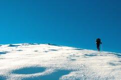 Fotvandraren klättrar till överkanten av berget Royaltyfri Fotografi