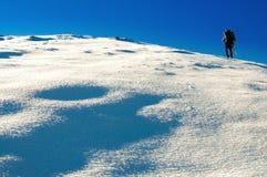 Fotvandraren klättrar till överkanten av berget Fotografering för Bildbyråer