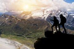 Fotvandraren med ryggsäckar når toppmötet av bergmaximumet Framgång, frihet och lycka, prestation i berg aktiv sport royaltyfria bilder