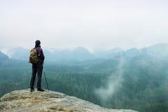 Fotvandraren med ryggsäcken och poler på klippan vaggar att hålla ögonen på över det dimmiga och dimmiga Springet Valley till hor Royaltyfri Fotografi