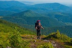 Fotvandraren med trekking poler stiger till överkanten Arkivfoto