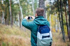 Fotvandraren tar ett foto med hans smartphone royaltyfria bilder