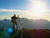 Fotvandraren tar selfiefotoet Mannen med den stora ryggsäcken och poler går på det alpina berget Arkivfoton
