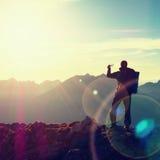 Fotvandraren tar selfiefotoet Mannen med den stora ryggsäcken och poler går på det alpina berget Royaltyfri Foto