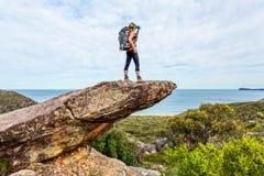 Fotvandraren vaggar på klippan som är klippbrants- med sikter arkivbilder