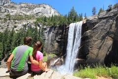 Fotvandrarepar som vilar i Yosemite, parkerar - vattenfallet Royaltyfria Foton