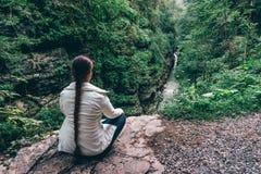 Fotvandraresammanträde på klippan av berget och att tycka om dalsikt med floden Arkivfoto