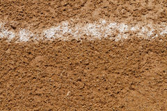 Foul Ball Chalk Line On A Baseball Field. A close up shot of a messed up foul ball white chalk line on a little league baseball field at a local public park Stock Photo