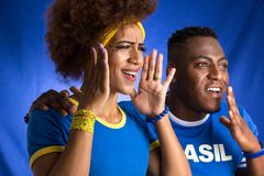 Foul. Brazilian black couple fans celebrating on soccer match on stock image
