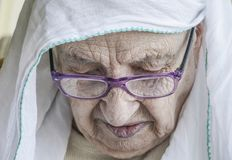 Foulard d'uso della donna senior mentre pregando Fotografia Stock