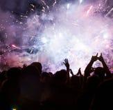 Foule célébrant la nouvelle année avec des feux d'artifice Photographie stock libre de droits