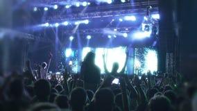 Foule des fans de musique dansant sous les rayons lumineux de l'illumination de LED, concert banque de vidéos