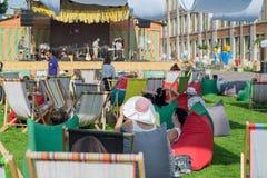 Foule des femmes et des hommes asseyant dans les ombres, détendant dans les canapés sur l'herbe en Europe Images stock