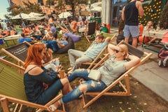 Foule des personnes détendant dans les canapés avec des boissons pendant le festival extérieur populaire de nourriture de rue Photos libres de droits