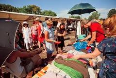 Foule des personnes observant de vieux vêtements de marché d'occasion images libres de droits