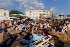 Foule des personnes prenant le déjeuner au foodcourt extérieur ensoleillé sous le ciel bleu, pendant le grand week-end de ville Images libres de droits