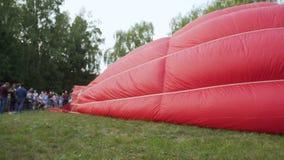 Foule des spectateurs observant le grand ballon remplir de l'air chaud avant vol clips vidéos