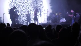 Foule faisant la partie à un concert de rock Les mains tiennent des caméras avec les affichages numériques parmi des personnes à  banque de vidéos