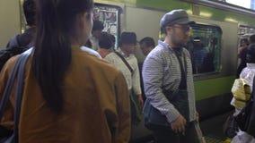 foule 4K de peuple japonais sur le chemin de fer de plate-forme, voyageant sur le train à Tokyo banque de vidéos
