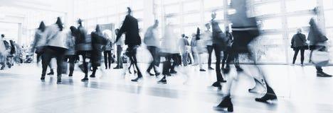 Foules des personnes dans le croisement de tache floue de mouvement dans un plancher Photographie stock libre de droits