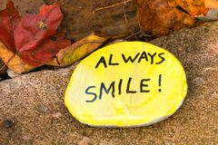 Found in the autumn leaves, a yellow hand painted flat stone. stock photography